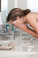 Woman washing face in bathroom