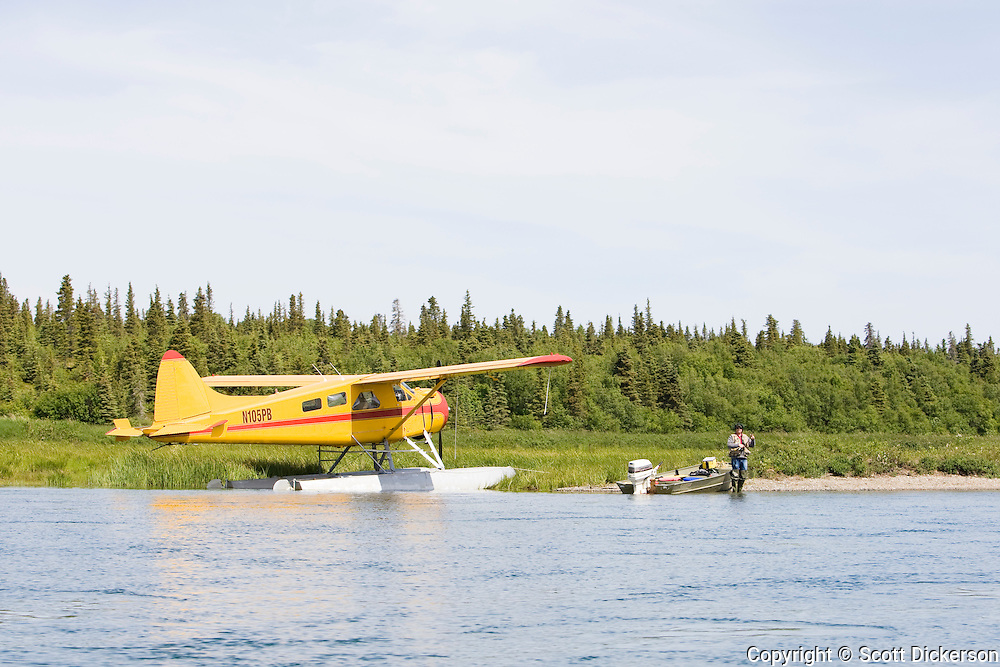 A sport fisherman angling for sockeye salmon next to a DeHavilland Beaver floatplane on the Kvichak River in Bristol Bay, Alaska.