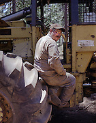 Carl Sutton, one of the central Sierra Nevada's few independent logging contractors, takes a break on his equipment near Arnold, California.