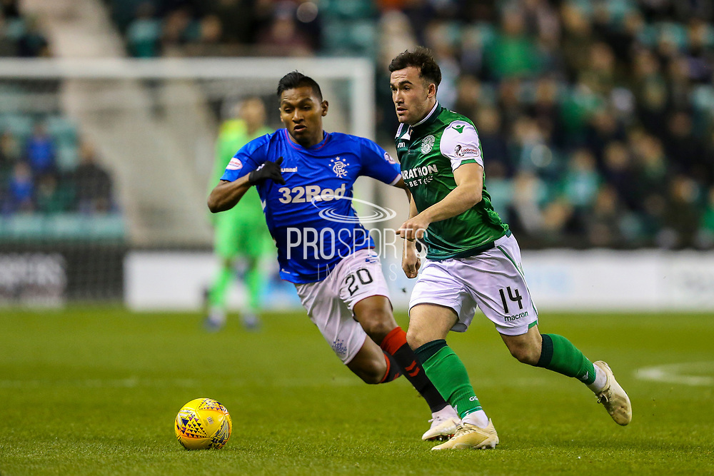 Stevie Mallan (#14) of Hibernian turns the ball away from Alfredo Morelos (#20) of Rangers during the Ladbrokes Scottish Premiership match between Hibernian and Rangers at Easter Road, Edinburgh, Scotland on 19 December 2018.