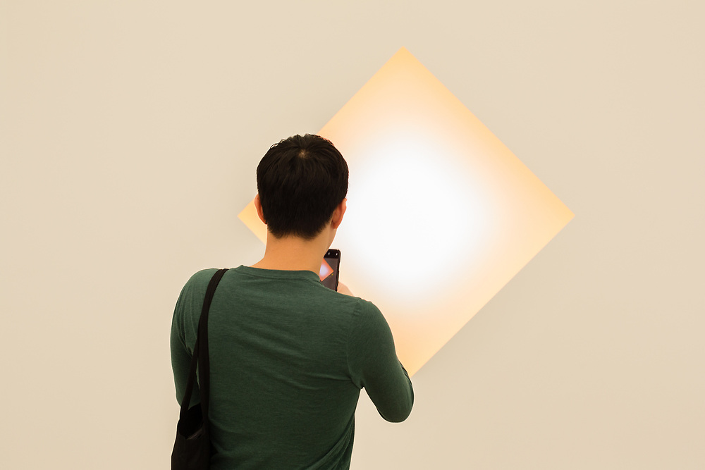 """New York, NY - May 3, 2019. A  man taking a photo of James Turrell's etched glass and LED """"Praamzius"""" in the Kayne Griffin Corcoran Gallery at the Frieze Art Fair on New York City's Randalls Island."""