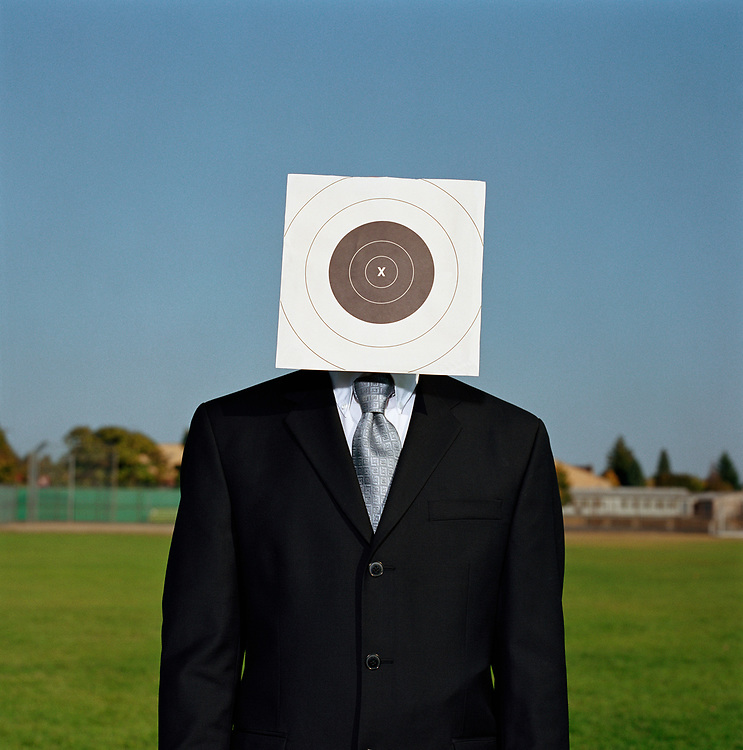 Man wearing suit with target in front of face
