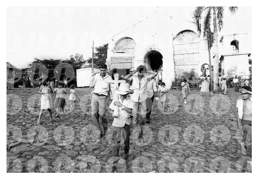 Familiares trasladan el cuerpo de un campesino que murió durante un bombardeo en San José las Flores, Chalantenango El Salvador durante de la guerra civil de El Salvador 1980-1992. . (IL Photo Franklin Rivera)