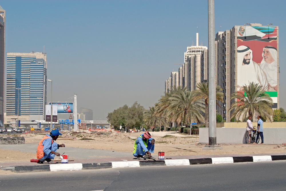 construction worker in the center of Dubai at Sheikh Zayed Road .A wall painting of Sheikh Zayed and Sheikh Maktoum bin Raschid Al Maktum right|