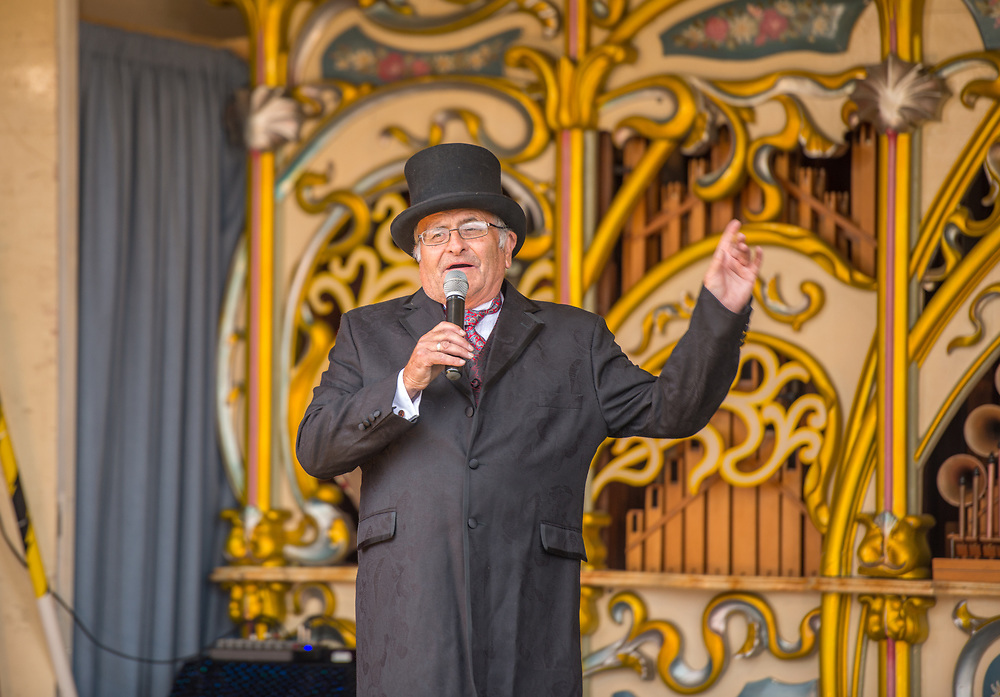 Mature male in a top hat uses microphone to speak to sectors while on top of fairground organ, Masham, North Yorkshire, UK