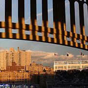 The late evening sunshine catches the Yankee Stadium facade as flags of American baseballs teams fly above the stands during the New York Yankees V Baltimore Orioles American League Division Series play-off decider at Yankee Stadium, The Bronx, New York. 12th October 2012. Photo Tim Clayton