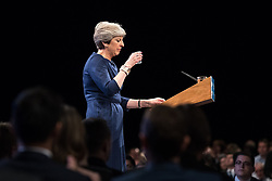 © Licensed to London News Pictures . 04/10/2017. Manchester, UK. Prime Minister THERESA MAY sips from a glass of water as she struggles with her throat and voice as she delivers her keynote speech on the fourth and final day of the Conservative Party Conference at the Manchester Central Convention Centre . Photo credit: Joel Goodman/LNP