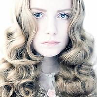 Close up head shot of young teenage female with long wavy fair hair and blue eyes looking at camera