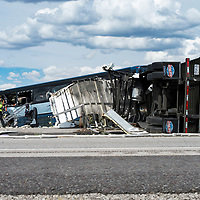 New Mexico State Police and rescue teams investigate the crash scene. A semi-tractor trailer traveling on I-40 eastbound had a tire blowout and crossed over into westbound lane, resulting in a collision with a Greyhound bus traveling to Los Angeles, CA. The incident occurred in Thoreau, NM Thursday afternoon. The accident killed at least seven people, according to New Mexico State Police.