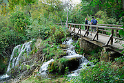 Two people walking over bridge and walkway over waterfall, Krka National Park, Croatia