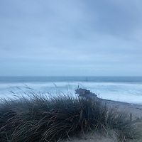 Stormy rough seascape with stone jetty and grass sand banks