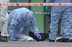 © Licensed to London News Pictures. 15/10/2015. London, UK. Forensics officers examine the road near Scriven Street in Hackney, east London where a male police officer was shot during an authorised firearms operation by the Trident gang crime unit of the Metropolitian Police.  A man has been arrested at the scene. Photo credit: Peter Macdiarmid/LNP