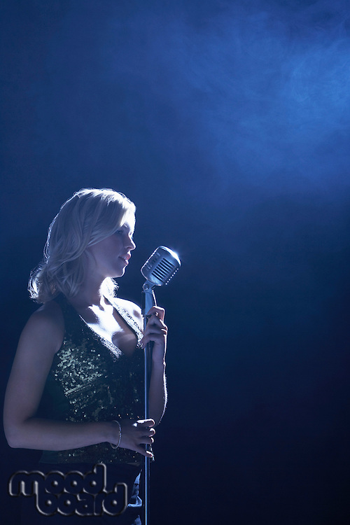 Woman Singing at Microphone in smoky place side view