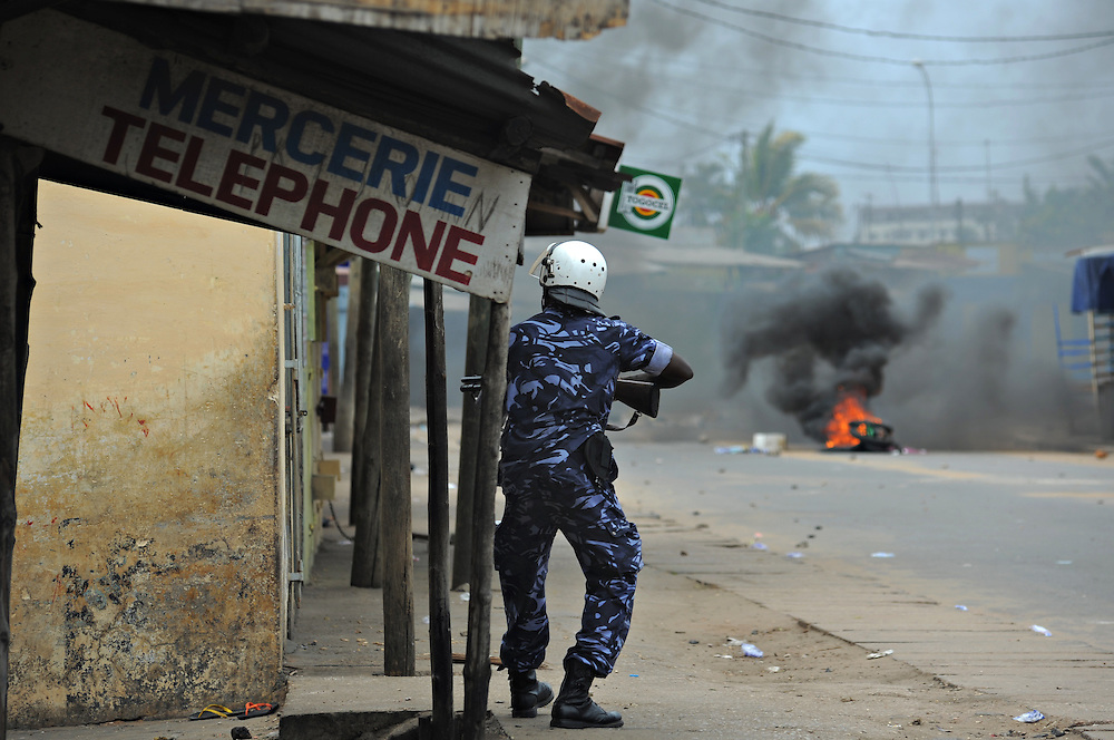 LOME, TOGO - 12-10-05   - A police officer attempts to secure a street as protesters clash with police in Lomé on October 5. A peaceful protest was scheduled by opposition groups, but their route was blocked by police.  For months, opposition parties have been calling for the departure of president Faure Gnassingbe, whose family has been in power for over 40 years.   Photo by Daniel Hayduk