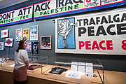 UNITED KINGDOM, London: 21 March 2017 A member of staff at The Imperial War Museum takes a close look at a collection of anti-war posters and banners which form part of the 'People Power: Fighting for Peace' exhibition at the Imperial War Museum. The exhibition explores the evolution of the anti-war movement from the First World War to the present day. Rick Findler / Story Picture Agency