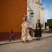 Two giant papier-mâché puppets, known as mojigangas, rush towards the Parroquia in San Miguel de Allende, Mexico. These looming puppets are farcical exaggerations of humanity, a tradition that can be traced to Spain. Pictured here are a bride and groom about to preside over a wedding celebration through the streets.