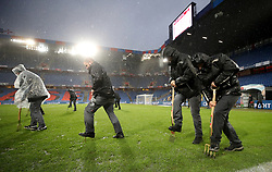 Ground staff use pitchforks to help drain the rainwater from the pitch before the FIFA World Cup Qualifying second leg match at St Jakob Park, Basel.