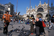 Family feeding pigeons in square of St. Mark's Basilica (Basilica di San Marco in Venezia), the most famous of the churches of Venice, Italy. The structure is one of the best examples of Byzantine architecture in the world. The building was also nicknamed Chiesa d'Oro ( church of gold ) due to it's lavish design and gilded Byzantine mosaics. The church dates back to 828 A.D and the basilica was consecrated in 1094 A.D...Subject photograph(s) are copyright Edward McCain. All rights are reserved except those specifically granted by Edward McCain in writing prior to publication...McCain Photography.211 S 4th Avenue.Tucson, AZ 85701-2103.(520) 623-1998.mobile: (520) 990-0999.fax: (520) 623-1190.http://www.mccainphoto.com.edward@mccainphoto.com.