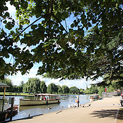 Boats on the River Avon at Stratford-upon-Avon, a market town and civil parish in south Warwickshire, England. It lies on the River Avon. The town is a popular tourist destination owing to its status as birthplace of the playwright and poet William Shakespeare, receiving about 3 million visitors a year. The Royal Shakespeare Company resides in Stratford's Royal Shakespeare Theatre. Photo Tim Clayton