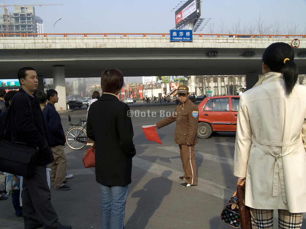 traffic police holding a red flag to signal the stop sign for pedestrian Beijing China