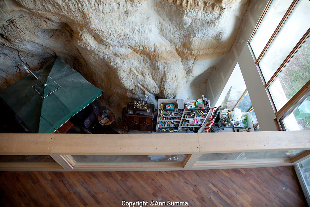 """Festus, Missouri: Looking down fron the third floor to the """"hallway"""" on the second floor, and below to the living area of the first floor, of Curt and Deborah Sleeper's 2,000 square foot home. The umbrella keeps the sand that sheds from the cave walls off a tale and chairs. The home is built inside a 17,000 square foot cave in this small town south of St. Louis."""