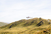Construction Helicopter carries a load of concrete to pour the foundations of a new cable car pylon. Photographed on Konigsleiten mountain top. Zillertal, Tyrol, Austria
