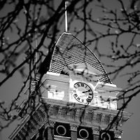 Courthouse clock tower on the Lake County Courthouse in Crown Point Indiana. The Lake County Courthouse was built in 1878 and is nicknamed The Grand Old Lady. The courthouse architecture is Romanesque and Georgian. Today it's used for events and has a ballroom and restaurants. Photo is black and white and high resolution.