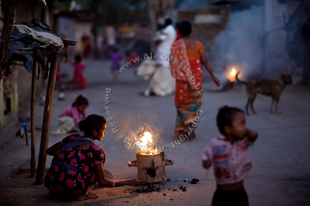 A woman is tending to the fire, in the late afternoon, on the streets of Oriya Basti, in Bhopal, Madhya Pradesh, India, site of the 1984 Union Carbide (now DOW Chemical) gas disaster.