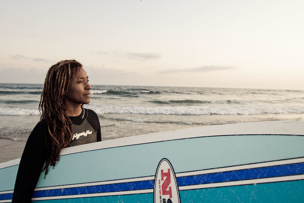A female surfer poses in front of the surf break (Beach 91) at Rockaway Beach, Queens, NY.