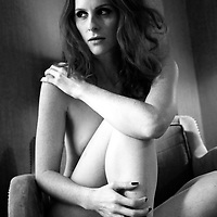 A naked woman sitting in a chair