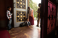 Konjit, 26, prays at the entrance to Kidist Selassie (Holy Trinity) Cathedral as her two sons sit just inside the door during a service at the church in Addis Ababa, Ethiopia, November 16, 2013. Konjit went for an abortion several days earlier, after her birth control failed, and says that because of her sin she is not allowing herself inside of the church-- the highest ranking Orthodox cathedral in the capital city.