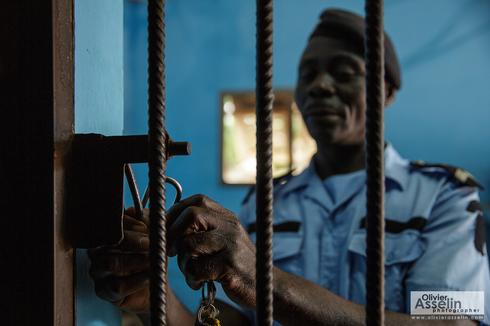 An officer locks up a cell where prisoners are kept at the police station in Katiola, Cote d'Ivoire on Saturday July 13, 2013.