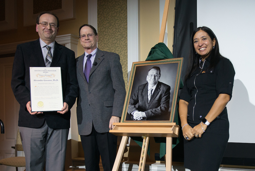 Ohio University's Interim President, David Descutner, left, and 2016 Distinguished Professor recipient, Dr. Gerardine Botte, right, unveil the 2017 Distinguished Professor portrait of Dr.  Alexander Govorov at Ohio University's Baker Center Ballroom on Monday, February 20, 2017.