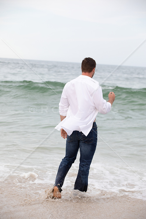 back of a man in jeans and open shirt at the ocean