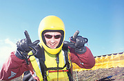 A man, smiling and gesturing to camera, wearing sunglasses, helmet and boilersuit, Paragliding, UK 2004