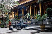 Old woman praying at quan su temple, Hanoi, Vietnam.