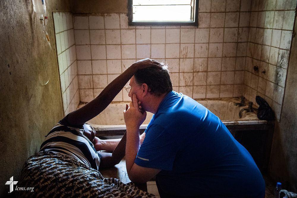 Fatmata sings a song praising God as she touches the hair of the Rev. Michael Awe, team leader and pastor at Hope Lutheran Church, South Sioux City, Neb., as he holds her other hand while she undergoes an IV on the fifth day of the LCMS Mercy Medical Team on Friday, May 11, 2018, in the Yardu village outside Koidu, Sierra Leone, West Africa. LCMS Communications/Erik M. Lunsford