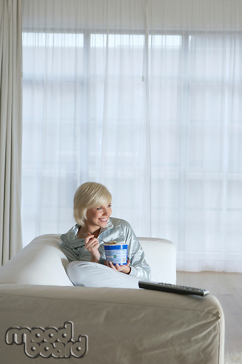 Woman sitting on sofa watching television and eating ice cream