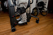 Rudy exercises on a standing frame machine that helps him bear weight on his legs and feet to prevent bone loss and aid in his rehabilitation. Oxnard, Calif. (photo by Gabriel Romero ©2011)
