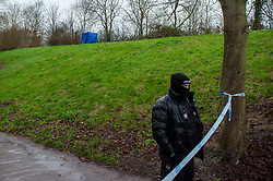 © Licensed to London News Pictures. 12/12/2019. Milton Keynes, UK. A forensic tent sits in a wooded area and a police officer maintains a cordon across a walkway in the Fishermead area after a man was stabbed. Thames Valley Police has launched a murder investigation following the death of a man in Milton Keynes. Police and South Central Ambulance Service attended a woodland in Fishermead, Milton Keynes at around 15:20GMT on Wednesday 11th December 2019 after a report of an altercation between a group of men, during which a man had been stabbed. The victim, a man aged in his twenties died at the scene. Photo credit: Peter Manning/LNP