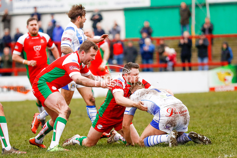 Keighley Cougars scrum half Matty Beharrell (7) tackles Workington Town full back Jamie Foster (1)  during the Betfred League 1 match between Keighley Cougars and Workington Town at Cougar Park, Keighley, United Kingdom on 18 February 2018. Picture by Simon Davies.