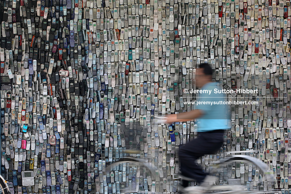 Pedestrians walk past a wall of mobile phones, made by Masanao Watanabe, on the exterior of his family run mobile telephone shop, 'Wataden', in Koiwa, east Tokyo, Japan, Friday, Aug 24th, 2007.  Mr. Watanabe began collecting mobile telephones in 1994, and now has over 6,000. The electronics shop has been in his family since 1928.