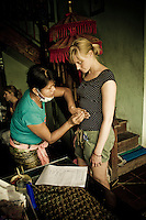 Wayan performs a 'body reading' on a Western customer at her Balinese Traditional Healing Center made famous by the book 'Eat, Pray, Love' in Ubud, Bali, Indonesia.