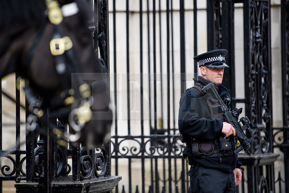 © Licensed to London News Pictures. 23/03/2017. London, UK. Armed police watch over members of the Household Cavalry on horse guards, during a guard changing ceremony, the day after a lone terrorist killed 4 people and injured several more, in an attack using a car and a knife. The attacker managed to gain entry to the grounds of the Houses of Parliament, killing one police officer. Photo credit: Ben Cawthra/LNP
