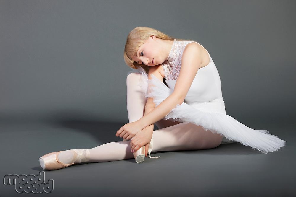 Upset young female ballet dancer sitting over grey background