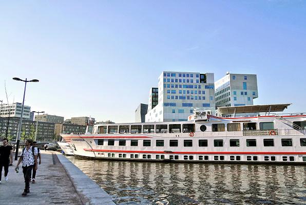 Nederland, Amsterdam, 29-7-2018 Schepen van een riviercruise aan de Ruijterkade in de haven bij het CS in Amsterdam . Op de achtergrond het IJ en de amsterdam Lookout .Foto: Flip Franssen
