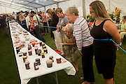 Locals admire jams and conserves lined up on a long table inside a marquee at Lambeth Country Show.