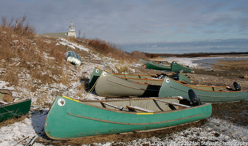 Boats line the shore of the Attawapiskat River, with the Catholic church behind. Many Cree in the community still hunt, fish and gather much of their diet in the traditional way. <br /> <br /> (Ian Stewart photo)