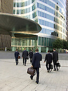 business men walking towards there office building