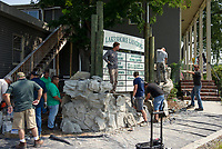 James King (standing) and Jason Rivera (in brimmed hat) with their crew from Clifrock install a waterfall using panel masonry technology outside of Lakeshore Landing with Diversified Dock and Marine / Scuba Supply on Friday afternoon.  (Karen Bobotas/for the Laconia Daily Sun)